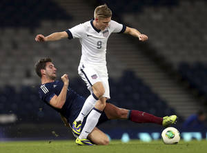 Photo - FILE - In this Nov. 15, 2013, file photo, United States' Aron Johannsson, right, vies for the ball with Scotland's Charlie Mulgrew, left, during an international soccer match at Hampden Park, Glasgow, Scotland. Johannsson is relatively new to the U.S. national team. The 23-year-old was born in Alabama to Icelandic parents, but moved back to Iceland in his youth and was a member of that nation's under-21 national side. He missed out on his first opportunity to play for Iceland's senior national team in late 2012 because of a groin injury and last year filed to make himself eligible to compete for the United States. (AP Photo/Scott Heppell, File)
