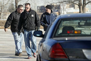Photo - Denver Police detectives investigate the scene of a stabbing on Friday, Dec. 13, 2013, in a parking lot adjacent to Sports Authority Stadium where three people were stabbed during a fight after an NFL football game between San Diego and Denver on Thursday. (AP Photo/Ed Andrieski)