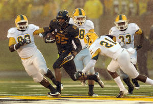 Photo -   Missouri wide receiver Marcus Lucas (85) is chased by Southeastern Louisiana defenders after catching a pass for a 21-yard gain as a steady rain falls during the second quarter of an NCAA college football game Saturday, Sept. 1, 2012, in Columbia, Mo. (AP Photo/L.G. Patterson)