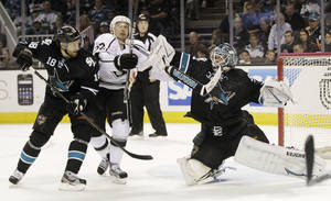 Photo -   San Jose Sharks goalie Antti Niemi, of Finland, right, hits Los Angeles Kings center Trevor Lewis (22) with his stick next to Sharks center Dominic Moore (18) during the second period of an NHL hockey game Saturday, April 7, 2012 in San Jose, Calif. (AP Photo/Marcio Jose Sanchez)