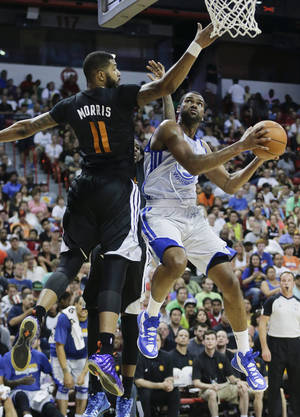 Photo - Golden State Warriors' James Southerland, right, goes up for a shot against Phoenix Suns' Markieff Morris in the second quarter of the NBA Summer League championship game, Monday, July 22, 2013, in Las Vegas. (AP Photo/Julie Jacobson)