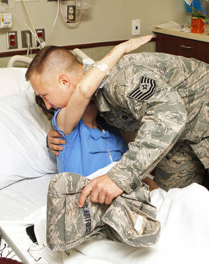 Tornado victim Sandra Adams hugs Air Force Tech. Sgt. Drew Stanley, 137th Air Refueling Wing, after returning his air force jacket to him Thursday in her hospital room at Integris Southwest Medical Center in Oklahoma City. Stanley came upon Adams during rescue efforts after her home was destroyed by Monday's tornado and wrapped her in his Air Force jacket before she was taken to the hospital. Photo by Paul B. Southerland, The Oklahoman