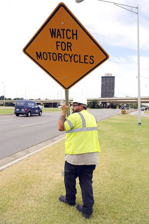 "Photo - Ryan Tennill installs a ""Watch For Motorcycles"" sign on the Northwest Expressway near Belle Isle Boulevard in Oklahoma City, Wednesday September 18, 2013. Photo By Steve Gooch, The Oklahoman"