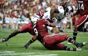 Photo - Mississippi State wide receiver Jameon Lewis (4) is tackled by South Carolina linebacker Kaiwan Lewis (8) during the first half of an NCAA college football game, Saturday, Nov. 2, 2013, in Columbia, S.C. (AP Photo/Rainier Ehrhardt)