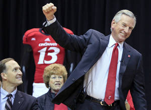 Photo - Tommy Tuberville pumps his fist as he is introduced as the new head football coach at the University of Cincinnati, Saturday, Dec. 8, 2012, in Cincinnati. Cincinnati athletic director Whit Babcock, left, watches. Tuberville had been head coach at Texas Tech, and previously at Auburn and Mississippi. (AP Photo/Al Behrman)