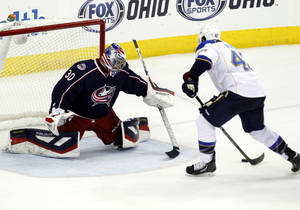 Photo - St. Louis Blues' David Backes, right, moves in to score the winning goal against Columbus Blue Jackets goalie Mike McKenna in overtime of an NHL hockey game in Columbus, Ohio, Saturday, Dec. 14, 2013. St. Louis won 4-3. (AP Photo/Paul Vernon)