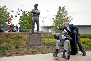 Photo - Ray Ackerman gets some help Friday from sculptor Jack Nortz to unveil a statue dedicated to Ackerman near the Chesapeake Boathouse in Oklahoma City. The statue honors Ackerman's advocacy of the Oklahoma River. Photo by Chris Landsberger, The Oklahoman