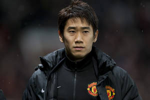 Photo - FILE - In this Wednesday Jan. 1, 2014 file photo, Manchester United's Shinji Kagawa heads for the substitutes bench before his team's English Premier League soccer match against Tottenham at Old Trafford Stadium, Manchester, England. Kagawa has started just seven of Manchester United's 21 league games so far this season, a struggle that has been well-documented in both Europe and Asia, but the playmaker is almost certain to be in the starting lineup for Japan in its opening World Cup match against Ivory Coast on June 14. (AP Photo/Jon Super)