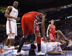 Photo - Oklahoma City's Kevin Durant (35) reacts after hitting the floor as Houston's Courtney Lee (5) checks on him during the NBA basketball game between the Oklahoma City Thunder and the Houston Rockets at the Chesapeake Energy Arena, Tuesday, March 13, 2012. Photo by Sarah Phipps, The Oklahoman.