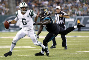 Photo - New York Jets quarterback Mark Sanchez, left, scrambles as Jacksonville Jaguars defensive tackle Sen'Derrick Marks chases him during the first half of an NFL preseason football game, Saturday, Aug. 17, 2013, in East Rutherford, N.J. (AP Photo/John Minchillo)