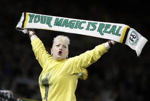 Photo - FILE - In this Nov. 24, 2013, file photo, a Portland Timbers fan holds up a scarf during the second half of the second game of the Western Conference finals in the MLS Cup soccer playoffs against Real Salt Lakein Portland, Ore.  The Timbers host the Philadelphia Union in their season opening game on Saturday, March 8, 2014. (AP Photo/Don Ryan, File)