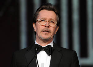 "Photo - FILE - This Jan. 4, 2014 file photo shows actor Gary Oldman speaking at the Palm Springs International Film Festival Awards Gala at the Palm Springs Convention Center in Palm Springs, Calif. Oldman is defending fellow actors Mel Gibson and Alec Baldwin from critics of their comments on Jews and homosexuals, saying people need to take a joke. In an interview with Playboy, Oldman decried ""political correctness"" that ensnared the two actors. (Photo by Frank Micelotta/Invision/AP, File)"