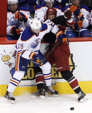 Photo - Edmonton Oilers defenseman Justin Schultz (19) and Phoenix Coyotes right wing David Moss battle for the puck in the second period of an NHL hockey game, Tuesday, Dec. 31, 2013, in Glendale, Ariz. (AP Photo/Rick Scuteri)