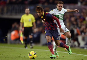 Photo - FC Barcelona's Neymar, right, duels for the ball against Elche's Aaron Niguez during a Spanish La Liga soccer match at the Camp Nou stadium in Barcelona, Spain, Sunday, Jan 5, 2014. (AP Photo/Manu Fernandez)