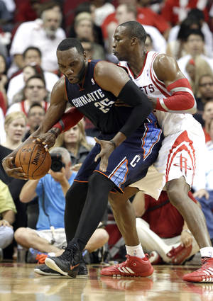 Photo - Houston Rockets center Dwight Howard, right, tries to steal the ball from Charlotte Bobcats' Al Jefferson in the second half of an NBA basketball game Wednesday, Oct. 30, 2013, in Houston. The Rockets won 96-83. (AP Photo/Pat Sullivan)