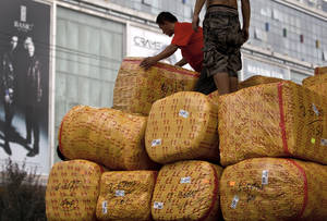 photo -   Workers load goods on a truck near a wholesale market for fashion clothing in Beijing Monday, Sept. 10, 2012. China's imports shrank unexpectedly in August in a sign its economic slump is worsening and the Chinese president warned growth could slow further, prompting expectations of possible new stimulus spending. (AP Photo/Andy Wong)