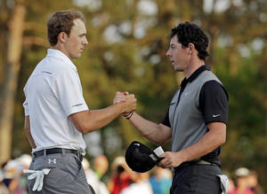Photo - Jordan Spieth, left, shakes hands with Rory McIlroy, of Northern Ireland, on the 18th green following their second round of the Masters golf tournament Friday, April 11, 2014, in Augusta, Ga. (AP Photo/Charlie Riedel)