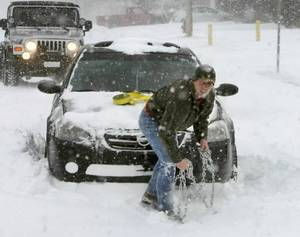 Photo - With bare hands, good Samaritan Josh Fulgium assists a motorist whose car was stuck in drifting snow in Edmond, OK, Tuesday, Feb. 1, 2011. By Paul Hellstern
