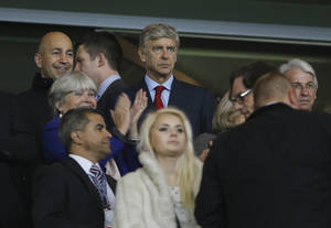 Photo -   Arsenal's manager Arsene Wenger, centre, watches from the stands as his team prepares to play FC Schalke 04 in their Champions League group B soccer match between Arsenal and FC Schalke 04 at the Emirates Stadium in London, Wednesday, Oct. 24, 2012. (AP Photo/Kirsty Wigglesworth)