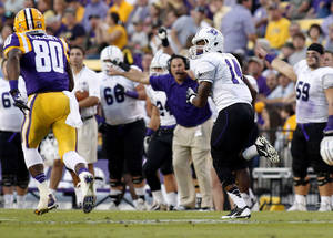 Photo - Furman cornerback Reggie Thomas (14) returns an interception for a 74- yard tuchdown during the first quarter of the NCAA college football game against LSU in Baton Rouge, La., Saturday, Oct, 26, 2013. (AP Photo/Jonathan Bachman)