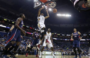 Photo - New Orleans Pelicans power forward Anthony Davis (23) slam-dunks over Atlanta Hawks power forward Paul Millsap (4), small forward DeMarre Carroll (5) and power forward Gustavo Ayon (14) in the first half of an NBA basketball game in New Orleans, Wednesday, Feb. 5, 2014. (AP Photo/Gerald Herbert)