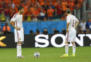 Photo - Spain's Diego Costa, left, and Spain's Andres Iniesta react after Netherlands' Arjen Robben scored during the group B World Cup soccer match between Spain and the Netherlands at the Arena Ponte Nova in Salvador, Brazil, Friday, June 13, 2014. (AP Photo/Manu Fernandez)