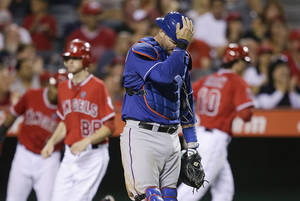 Photo - Texas Rangers catcher A.J. Pierzynski reacts after Los Angeles Angels' Grant Green, background right, scored on a hit by J.B. Shuck during the sixth inning of a baseball game Saturday, Sept. 7, 2013, in Anaheim, Calif. (AP Photo/Jae C. Hong)