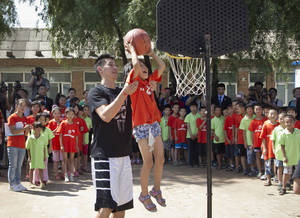 Photo -   The Houston Rockets Jeremy Lin helps a child to slum a dunk during a basketball clinic at a school in Changping, on the outskirts of Beijing, Thursday, Aug. 9, 2012. (AP Photo/Andy Wong)