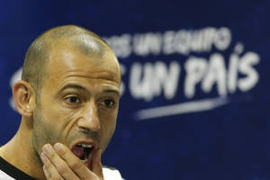 "Photo - Argentina's Javier Mascherano gestures at the start of a news conference in Vespesiano, near Belo Horizonte, Brazil, Sunday, July 6, 2014. The sign reads in Spanish ""one country."" Argentina will face Netherlands on their semifinal match of the 2014 World Cup soccer tournament on July 9 in Sao Paulo.(AP Photo/Victor R. Caivano)"