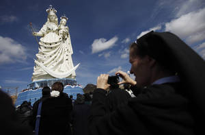 "photo - A nun takes pictures of a newly unveiled statue of the Virgin Mary holding a baby Jesus on Santa Barbara hill in the mining city of Oruro, Bolivia, Friday, Feb. 1, 2013. The 45 meter (147 feet) statue that took four years to build, known in Spanish as ""Virgen del Socavón,"" or the Virgin of the Tunnel, is Oruro's patron, venerated in particular by miners and folkloric Carnival dancers. (AP Photo/Juan Karita)"