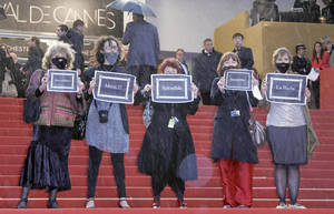Photo -   Demonstrators from the French feminist group 'La Barbe' hold signs in protest on the red carpet at the 65th international film festival, in Cannes, southern France, Sunday, May 20, 2012. The group protested against what they feel is a lack of representation of female filmmakers at the festival. Signs read from left to right, Marvelous, Thank You, Splendid, Incredible, The Beard. (AP Photo/Francois Mori)