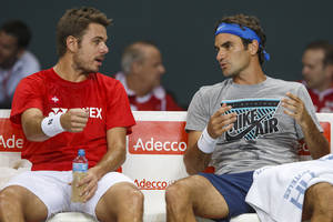 Photo - Stanislas Wawrinka, left, of Switzerland, and Roger Federer, right, of Switzerland, speak together during a training session of the Swiss Davis Cup tennis team prior to the Davis Cup World Group quarterfinal match between Switzerland and Kazakhstan, , in Geneva, Switzerland, Wednesday, April 2, 2014. The Davis Cup World Group quarterfinal between Switzerland and  Kazakhstan will take place from April  4 to April 6. (AP Photo/Keystone,Salvatore Di Nolfi)