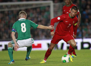 Photo - Portugal's Cristiano Ronaldo, right, wins the ball from Northern Ireland's Steven Davis during their World Cup Group F qualifier soccer match at Windsor Park, Belfast, Northern Ireland, Friday, Sept. 6, 2013. (AP Photo/Peter Morrison)