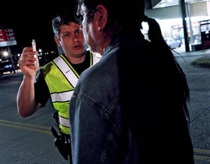 Photo - Deputy Sheriff Sean Shelby conducts a field sobriety test at a DUI checkpoint at NE 10th and Sooner, in Oklahoma County, operated by the Oklahoma County Sheriff's department , March 17, 2009. THE OKLAHOMAN ARCHIVES