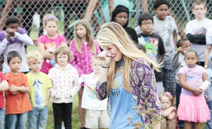 Photo - Brandon Santos's teacher Bailee Sossamon wipes a tear from her eye as she walks up to plant a tree  in his honor at Overholser Elementary School. Brandon and two of his siblings drowned in the May 31 storms.  Photo by David McDaniel, The Oklahoman <strong>David McDaniel - The Oklahoman</strong>
