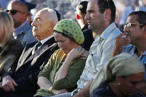 Photo - Rachel and Avi Fraenkel, parents of U.S.-Israeli national Naftali, 16, one of the three Israeli teens who were abducted and killed in the West Bank, mourn as they sit next to Israeli President Shimon Peres during their son'ss joint  funeral in the Israeli city of Modiin, Tuesday, July 1, 2014. Tens of thousands of mourners converged Tuesday in central Israel for the funeral service for three teenagers found dead in the West Bank after a two week search and crackdown on the Hamas militant group, which Israeli leaders have accused of abducting and killing the young men. The deaths of Eyal Yifrah, 19, Gilad Shaar, 16, and Naftali Fraenkel, a 16-year-old with dual Israeli-American citizenship, have prompted angry calls for revenge and Prime Minister Benjamin Netanyahu convened his security Cabinet for an emergency meeting to discuss a response to the killings, hours after airstrikes targeted dozens of suspected Hamas positions in the Gaza Strip.(AP Photo/Baz Ratner, Pool)