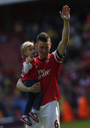Photo - Arsenal's Laurent Koscielny, carrying his unidentified daughter, waves to the supporters as the team parade around the stadium in their last home match at the end of their English Premier League soccer match against West Bromwich Albion at Emirates Stadium in London, Sunday, May 4, 2014. (AP Photo/Sang Tan)
