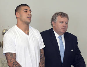 Photo - FILE - In this June 26, 2013, file photo, Aaron Hernandez, left, stands with his attorney, Michael Fee, right, during arraignment in Attleboro District Court in Attleboro, Mass. Since Hernandez was arrested last week in the shooting death of a friend whose body was found a mile away from his home, a portrait has emerged of a man whose life away from the field included frequent connections with police-related incidents that started as long ago as his freshman year at the University of Florida. (AP Photo/The Sun Chronicle, Mike George, Pool)