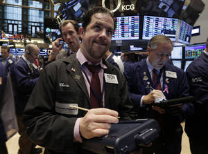 Photo - Trader Christopher Lotito, center, works on the floor of the New York Stock Exchange Thursday, Oct. 31, 2013. Stocks edged lower in early trading on Wall Street Thursday, paring the market's big gain for October. (AP Photo/Richard Drew)