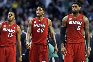 Photo - Miami Heat's Mario Chalmers (15), Udonis Haslem (40) and LeBron James (6) walk upcourt after a timeout in the first quarter of an NBA basketball game against the Boston Celtics in Boston, Monday, March 18, 2013. (AP Photo/Michael Dwyer)