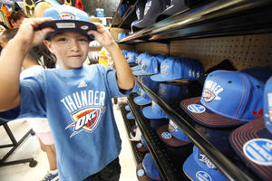 photo - Christian Sanchez, from the Earlywine Park YMCA Summer Day Camp, selects Thunder gear at Academy Sports + Outdoors. The retailer gave away 25 $50 gift cards. <strong>David McDaniel - The Oklahoman</strong>