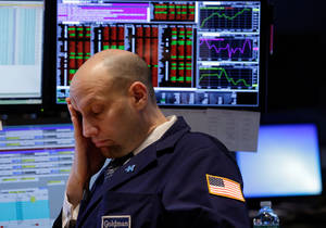 Photo - FILE - In this Wednesday, March 19, 2014, file photo, Specialist Meric Greenbaum works at his post on the floor of the New York Stock Exchange. 2014. U.S. stocks are falling in midday trading Monday, March 24, 2014, as tensions with Russia escalate. (AP Photo/Richard Drew, File)