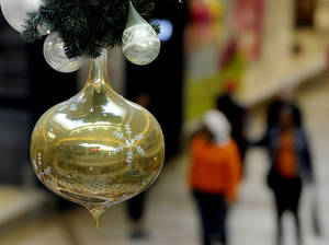 photo - A metallic Christmas ornament hangs from the ceiling at a Tampa, Fla., mall in the early morning Friday as consumers look for deals for the upcoming Christmas holiday. AP Photo