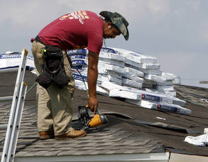 Photo - Roofers are active near the site of a tornado that damaged or destroyed homes near Telephone Road on Tuesday in Moore.  Photo by Steve Sisney, The Oklahoman <strong>STEVE SISNEY</strong>