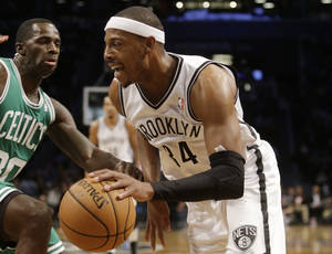 Photo - Brooklyn Nets' Paul Pierce, right, drives past Boston Celtics' Brandon Bass during the first half of a preseason NBA basketball game Tuesday, Oct. 15, 2013, in New York. (AP Photo/Frank Franklin II)
