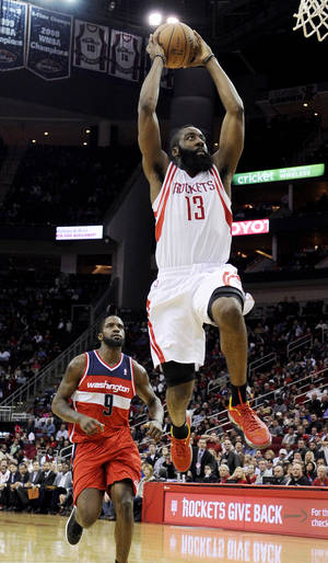 Photo - Houston Rockets' James Harden (13) goes to the basket in front of Washington Wizards' Martell Webster (9) in the second half of an NBA basketball game, Wednesday, Dec. 12, 2012, in Houston. The Rockets won 99-93. (AP Photo/Pat Sullivan)