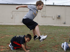 Photo - Ty Morrison, 8, leaps over Brandon Anderson, 6, during a game of leap frog at Kid's Maniac Fitness in Moore, Okla., Tuesday, April 9, 2013. Photo by Bryan Terry, The Oklahoman <strong>Bryan Terry</strong>