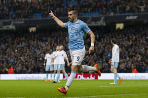 Photo - Manchester City's Alvaro Negredo celebrates after scoring against West Ham United during their English League Cup semifinal soccer match at the Etihad Stadium, Manchester, England, Wednesday Jan. 8, 2014. (AP Photo/Jon Super)