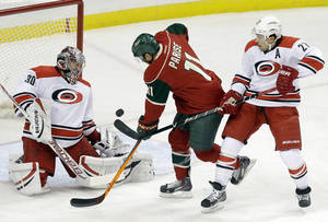 Photo - Carolina Hurricanes goalie Cam Ward, left, blocks a shot off the stick of Minnesota Wild's Zach Parise, center, as Hurricanes' Justin Faulk defends in the first period of an NHL hockey game Thursday, Oct. 24, 2013, in St. Paul, Minn. (AP Photo/Jim Mone)