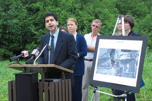 Photo - Hoosier Environmental Council Executive Director Jesse Kharbanda, at podium, speaks at a news conference on Monday, Aug. 11, 2014, in Indianapolis where environmental and public health groups called on the Marion County Health Department to compel a local utility to test groundwater around several coal ash lagoons on the city's south side. The group The Hoosier said Monday that coal ash from an Indianapolis Power & Light power plant could be could be carrying toxic chemicals such as mercury and arsenic into wells in nearby subdivisions. (AP Photo/Charles Wilson)